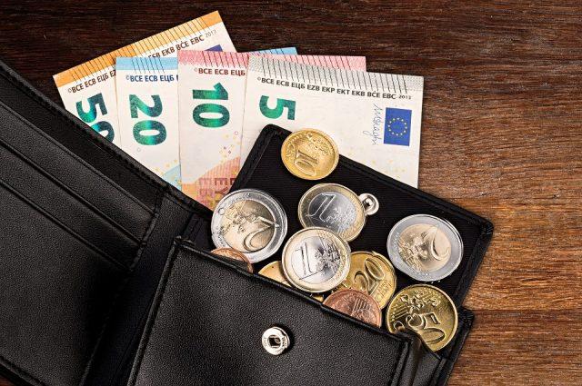 Pièce en euros et billet de banque dans un portefeuille en cuir noir