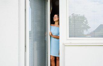 jeune femme ouvre la porte du balcon pvc